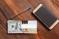 Packen av dollar ringer penn- och pappersklistermärken för din text på träbakgrund royaltyfri bild