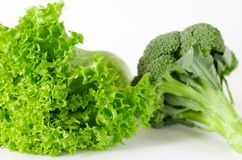 Packen av grönsallat och broccoli är på en vit bakgrund royaltyfria bilder