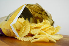 A packet of crinkle cut chips. Crinkle cut potato chips or crisps spilling out of a packet Royalty Free Stock Images