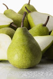 Packham Pears. A pear standing in front of whole and halved pears Royalty Free Stock Images