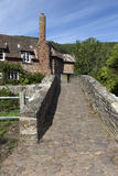 Packhorse bridge. Over the stream in the pretty village of Allerford in the county of Somerset in the UK Stock Image