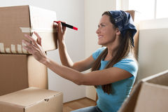 Packing. Young woman packing boxes at home Royalty Free Stock Images