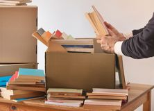 Packing books in a cardboard box royalty free stock image