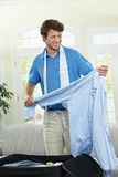 Packing for business trip. Young man packing for business trip. Holding blue shirt, smiling Royalty Free Stock Photos