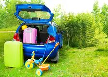 Packing a car for trip with kids. Packing the car with bags for trip, trickle, ball, scoop-net Royalty Free Stock Photo