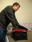 Packing the Carry-on. Photo of man packing a carry-on bag for a plane trip royalty free stock images