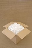 Packing Carton. Cardboard carton filled with packing chips on a corrugated board background Stock Photography
