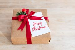 Packing Christmas gifts. Giftbox with ribbon and gift card with text - Merry Christmas. Top view. Packing Christmas gifts. Giftbox with ribbon and gift card stock images