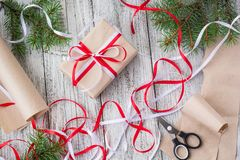 Packing Christmas presents in kraft paper with red and white ribbons.  Royalty Free Stock Images