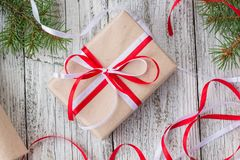 Packing Christmas presents in kraft paper with red and white ribbons.  Stock Image