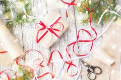 Packing Christmas presents in kraft paper with red and white ribbons.  royalty free stock photo