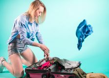 Packing clothes., young blond woman choosing necessary things for the trip . royalty free stock photography