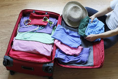 Packing clothing up preparatory to journey. A person is packing clothing up preparatory to her journey Stock Photography