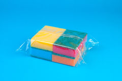Packing Colorful Synthetic sponges. On blue background Royalty Free Stock Photos