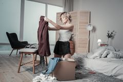 Woman packing clothes of ex husband into boxes and crying royalty free stock photos