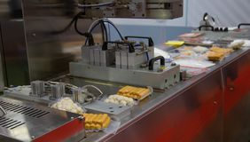 Food plastic packaging machine. Packing food sausage and meat ball in production line Stock Image
