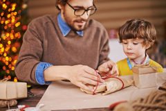 Packing gifts. Young men and his son packing xmas gifts Stock Photography