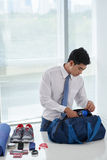 Packing gym bag. Young Vietnamese businessman packing bag for the gym Stock Photos