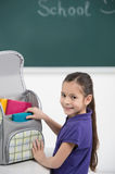 Packing her book bag. Cheerful little schoolgirl packing her boo royalty free stock photo