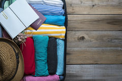 Packing a luggage for a new journey. On wood table Stock Photos