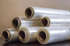 Packing material. Many rolls of stretch film are white transparent. Polymer product for wrapping. stock photos