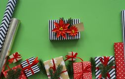 Packing a New Year`s gift. Green background. Many boxes of gifts, tied with ribbons. The colors are gold, green, red, yellow and k Royalty Free Stock Photography