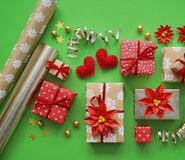 Packing a New Year`s gift. Green background. Many boxes of gifts, tied with ribbons. The colors are gold, green, red, yellow and k Royalty Free Stock Image
