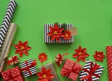 Packing a New Year`s gift. Green background. Many boxes of gifts, tied with ribbons. The colors are gold, green, red, yellow and k Stock Photography