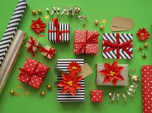 Packing a New Year`s gift. Green background. Many boxes of gifts, tied with ribbons. The colors are gold, green, red, yellow and k Stock Images