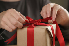 Packing presents with red ribbon Stock Photography