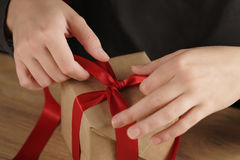 Packing presents with red ribbon Royalty Free Stock Image