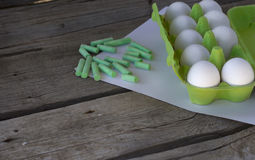 Packing raw eggs and green crayons. On a sheet of paper Stock Photo