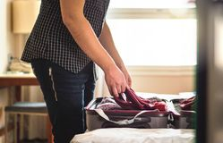Packing suitcase in hotel room. Young man folding t-shirt on bag. Gage in home bedroom. Open luggage on bed for vacation preparing. Person going on or leaving Stock Images