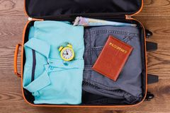 Packing suitcase for vacation top view. Flat lay. Male apparel, yellow alarm clock and passport Royalty Free Stock Photos