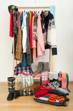 Packing the suitcase for winter vacation. Wardrobe with clothes nicely arranged and a full luggage. Stock Photo