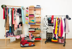 Packing the suitcase for winter vacation. Wardrobe with clothes nicely arranged and a full luggage. Stock Photos