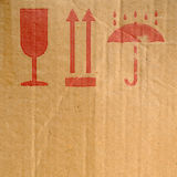Packing symbols. On old cardboard box Royalty Free Stock Images