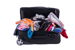 Packing to go on vacation isolated on white background. Messy suitcase full of clothes and accessories for vacation isolated on white background royalty free stock photo