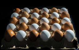 Packing of yellow and white chicken eggs arranged in a diagonal composition on a black background.  stock photos