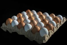 Packing of yellow and white chicken eggs arranged in a diagonal composition on a black background.  royalty free stock photo