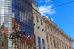Packningar tvättar fönstren av den moderna skyskrapan Arkivbild