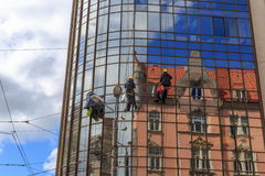 Packningar tvättar fönstren av den moderna skyskrapan Arkivfoto