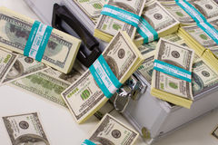 Packs of dollars. Packs of dollars scattered from a metal suitcase. Successful transaction Royalty Free Stock Photos