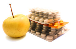 Packs of pills and yellow apple Royalty Free Stock Images