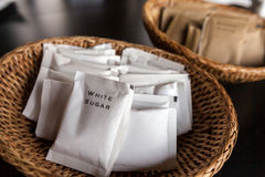 Packs of white sugar in bamboo tray. Many packs of white sugar in bamboo tray prepared for coffee break during seminar event royalty free stock images