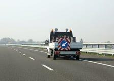 Packwagen für Landstraßenwartung mit dem Pfeil im Verkehrszeichen Stockbilder