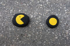 Pacman game concept with colored stones over street asphalt Royalty Free Stock Images