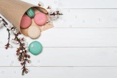 Pacote com bolinhos de amêndoa e as flores coloridos em um CCB de madeira branco Fotos de Stock