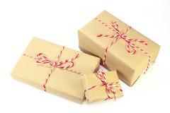 Pacote do papel de Brown amarrado com corda vermelha e branca Fotografia de Stock Royalty Free