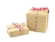 Pacote do papel de Brown amarrado com corda vermelha e branca no backg branco Imagens de Stock